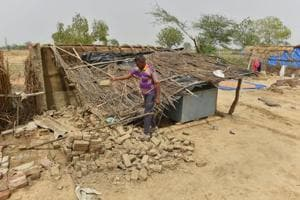 A man shows his thatched house damaged in Wednesday