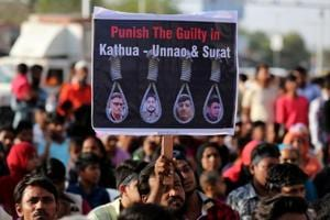 File photo of people holding placards at a protest against the rape of an eight-year-old girl, in Kathua, near Jammu, a teenager in Unnao, Uttar Pradesh state, and an eleven-year-old girl in Surat on April 22.