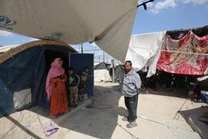 Displaced Iraqis stand outside a tent where they are taking shelter in a camp for internally displaced people near al-Khalidiyeh in Iraq