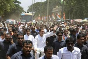Congress party president Rahul Gandhi rides a bicycle and waves to his supporters while campaigning in Malur on May 7.