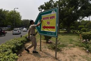 A policeman removes the poster of Maharana Pratap Road that was put up in place of the Akbar Road signboard in New Delhi.