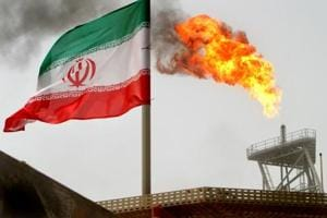 A gas flare on an oil production platform in the Soroush oil fields is seen alongside an Iranian flag in the Persian Gulf, Iran. President Donald Trump's decision to reimpose sanctions on Iran threatens to tighten global oil markets and could derail tens of billions of dollars in business deals.