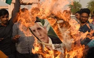 Youths burn a portrait of Mohammad Ali Jinnah in the state capital.