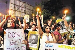 People hold candles and placards during a protest against the recent rape cases in the country, in Surat, Gujarat.