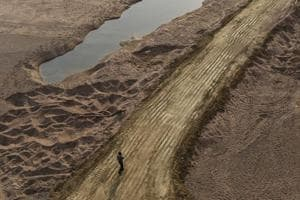 A man walks over truck tire tracks on Ken's rich river bed in Madhya Pradesh.