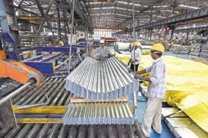 Employees guide finished corrugated steel roofing onto a pallet in the tube mill at a steel manufacturing facility.