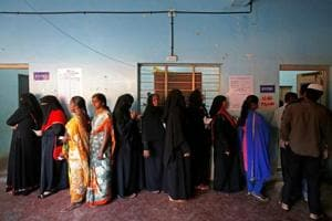 Voters wait in a queue to cast their ballot outside a polling station during Karnataka assembly elections in Bengaluru.