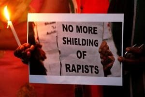 People participate in a candle light vigil as they protest against the rape of a child in Ahmedabad.