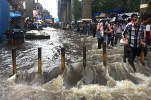 People wade through a waterlogged street in Mumbai  on August 29, 2017.