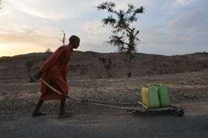 Bhopal, India - May 13, 2018: A priest carrying water for a temple in Budelkhand area near Prithvipur in Madhya Pradesh.