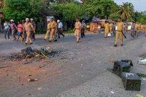 Security personnel walk past burnt ballot boxes lying on a road after miscreants ransacked at a polling station during panchayat polls at Rampur in South Dinajpur district of West Bengal, on Monday.