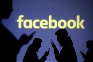 Silhouettes of mobile users are seen next to a screen projection of Facebook logo in this picture illustration taken on March 28.