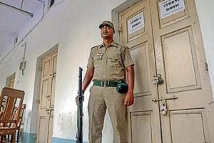 A security guard stands in front of a strong room after the panchayat poll at Nadia district in West Bengal on Tuesday.