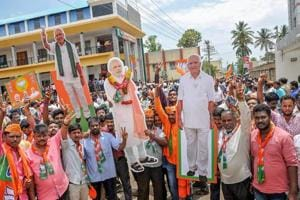 BJP workers hold cut-outs of PM Narendra Modi and BJP
