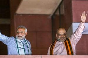 Prime Minister Narendra Modi and BJP President Amit Shah wave to party workers gathered at the party headquarters, after the Karnataka Assembly elections result 2018, in New Delhi, on Tuesday.