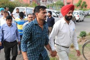 Sub-inspector Sewa Singh being taken to the duty magistrate in Sector 39, Chandigarh. Constable Sumit and middleman Ajay are the other two accused.