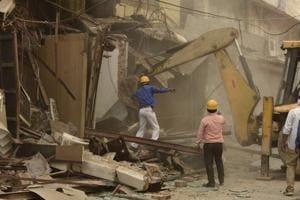 EDMC officials remove encroachments and demolishes some shops at Mangal Bazar in Laxmi Nagar, New Delhi.