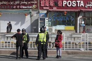 In this Nov. 3, 2017 photo, residents are seen with security personnel on the streets of Hotan in western China