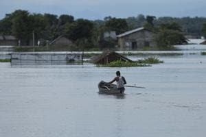 A man moves on a boat near submerged houses near Kaziranga national park in Assam.