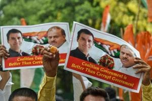 Congress supporters raise posters of party president Rahul Gandhi and JD(S) chief HD Kumarswamy after Karnataka chief minister BS Yeddyurappa announced his resignation, in New Delhi on May 19.