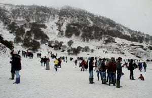 Tourists enjoy the view of snow covered hills around the Changu Lake after fresh snowfall in Sikkim on March 15,  2018.
