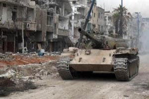 A handout picture released by the official Syrian Arab News Agency (SANA) on May 10, 2018 shows a Syrian army tank advancing through a street in al-Hajar al-Aswad as they push against the Islamic State (IS) group in the area on the southern outskirts of the capital Damascus.