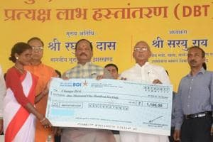 Chief minister Raghubar Das giving a cheque to a beneficiary during the inaugural function of Direct Benefit Transfer (DBT) scheme under food security at Nagri in Ranchi on October 4,2017.