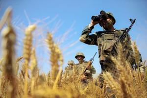 BSF personnel uses binoculars to maintain vigil along the international border in Jammu.