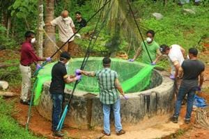 Animal Husbandry department and forest officials inspect a well to catch bats at Changaroth in Kozhikode in Kerala on May 21, 2018.