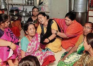 Family members of one of the victims, Roshan Singh, mourn their loss at Wagle Estate on Monday.