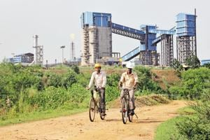 Men ride their bicycles in front of the Bhushan Steel plant in the eastern Indian state of Odisha