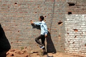 A border villager inspects the wall of a building damaged by shelling from the Pakistani side of the border in Nanga village of Ramgarh sector, around 45 km from Jammu, on May 23, 2018.