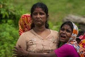 In this file photo taken on September 27, 2017, Hindu women cry near the dead bodies of their family members in Ye Baw Kyaw village, Maungdaw in Myanmar
