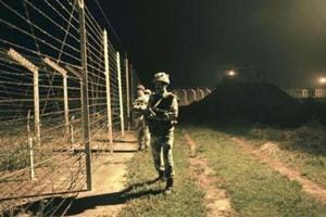 Border Security Force personnel stand guard near a fence at the India-Pakistan International Border at the Akhnoor outpost recently.