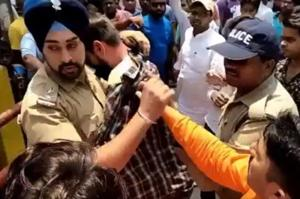 Sub-inspector Gagandeep Singh shileds and escorts the Muslim youth away from angry Hindu activists near Ramnagar town in Nainital district of Uttarakhand on Tuesday.