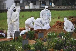 Paramedics wear protective suits as a precautionary measure against the Nipah virus as they bury a patient, died of the same virus, in Kozhikode on May 24.