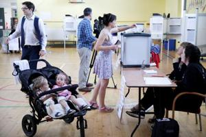 A woman votes while her children wait in their pushchair as Ireland holds a referendum on liberalizing its law on abortion, in Dublin, Ireland, May 25, 2018.