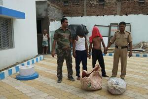 Manglu Khan and Sadekul Khan (faces covered) with Shamshergunj police on Friday.