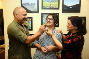Aastha Tiwary with her parents at her home on Saturday. She topped the CBSE board exams in the city, scoring 98.4 per cent in the Humanities stream.