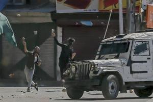 Kashmiri protesters throw rocks and bricks at a police vehicle in Srinagar on May 25, 2018.