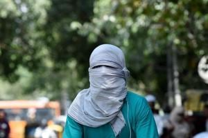 A man covers his face to protect himself from heat during a hot summer day in the old quarters of New Delhi on May 25, 2018.