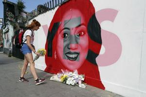 A woman places flowers by a mural showing Savita Halappanavar, a 31-year-old Indian dentist who had sought and been denied an abortion before she died after a miscarriage in a Galway hospital, with the word YES over it, in Dublin, Ireland, on the day of a referendum on the 8th amendment of the constitution.