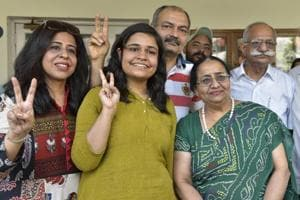 Astha Bamba of BCM Arya Model School Shastri Nagar along with her parents showing the victory sign after she scored 497 marks in humanities stream and joint third topper in India in CBSE class 12th result , in Ludhiana on Saturday.