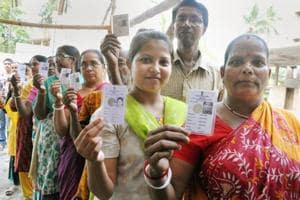 Voters show their Election Commission cards as they queue to cast their vote at a polling station during Maheshtala ssembly by-election, at Maheshtala in South 24 Parganas district of West Bengal, on Monday.