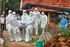 Doctors and relatives wearing protective gear carry the body of a Nipah victim during his funeral at a burial ground in Kozhikode, Kerala.