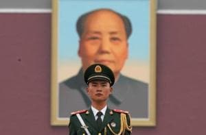 A paramilitary policeman stands guard before a giant portrait of late Chinese Chairman Mao Zedong at Tiananmen Gate.  Mao continues to be deeply revered in China.