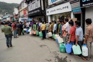 People queue up at Mall Road in Shimla on Sunday to collect water from a tanker as the city faces acute shortage of drinking water.