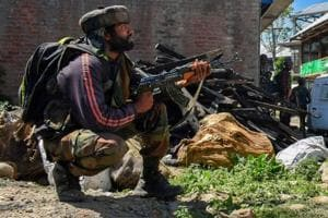 Security personnel stand guard during an encounter between security forces and militants in Pulwama.