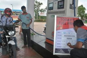 An employee updates fuel prices display board at a petrol pump, in Howrah on Wednesday, May 30, 2018