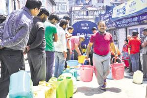 Residents wait in queue to fill buckets and cans with water from a tanker at Lower Bazaar in Shimla on Tuesday.